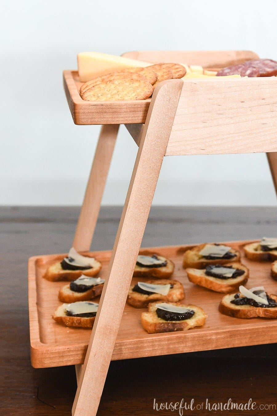 Close up view of the white maple stand holding the 2 wood serving trays.
