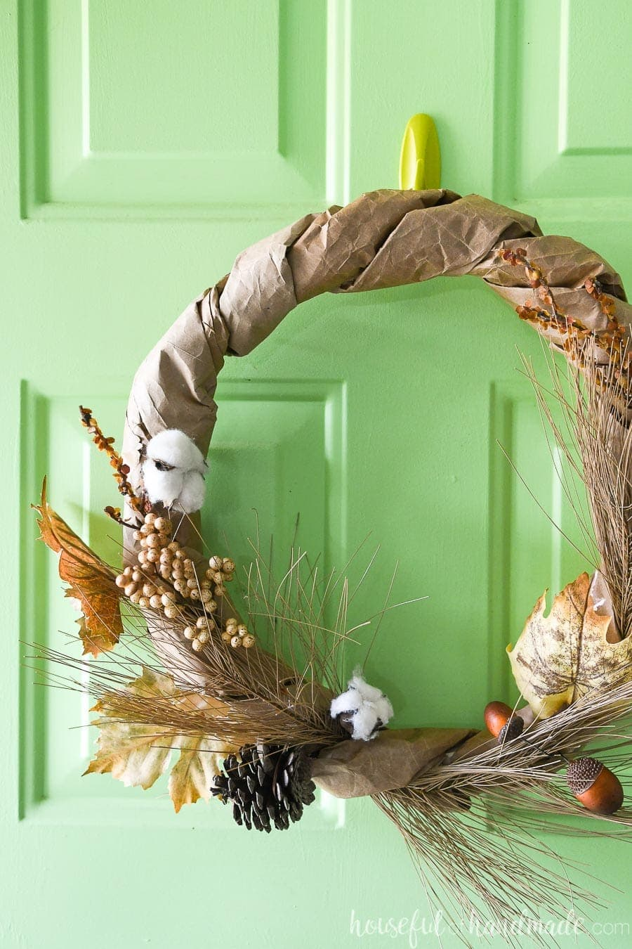 View of the left side of the neutral fall wreath made from a brown paper bag hanging on a green front door.
