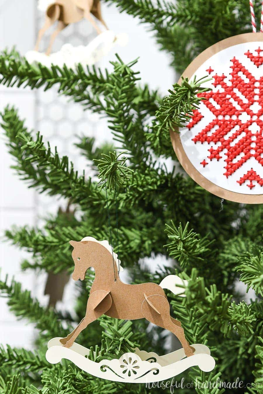 Rocking horse Christmas ornament made out of cardstock hanging on the Christmas tree.