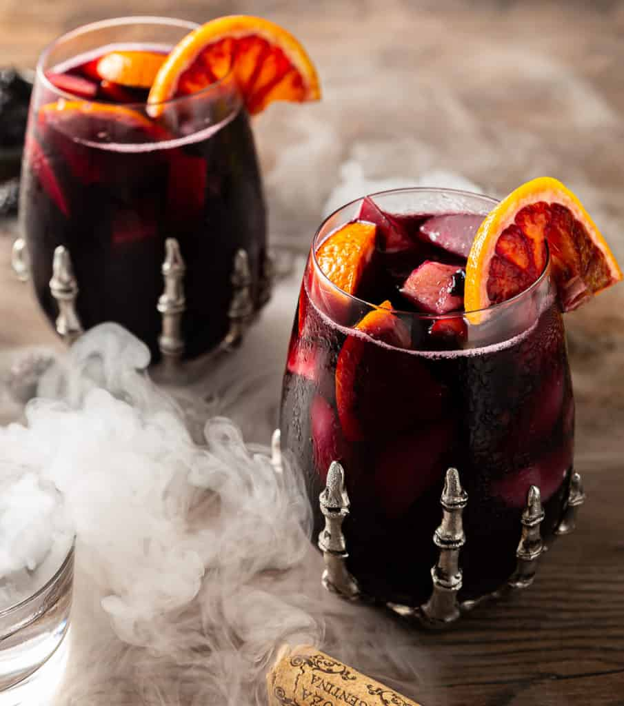 red halloween sangria with apples, oranges, and blackberries with smoke in a skeleton glass