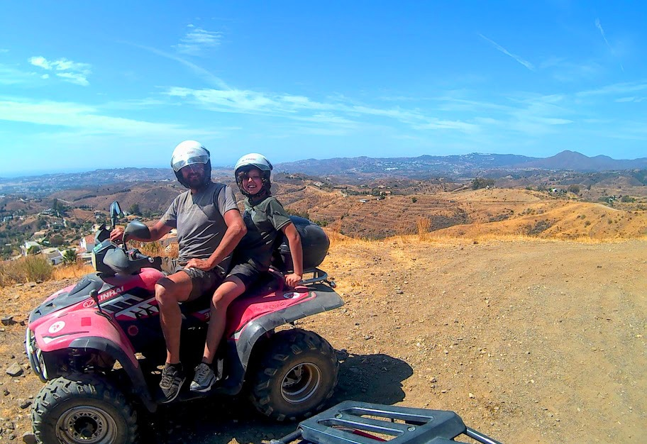 top of a mountain smiling couple on a quad