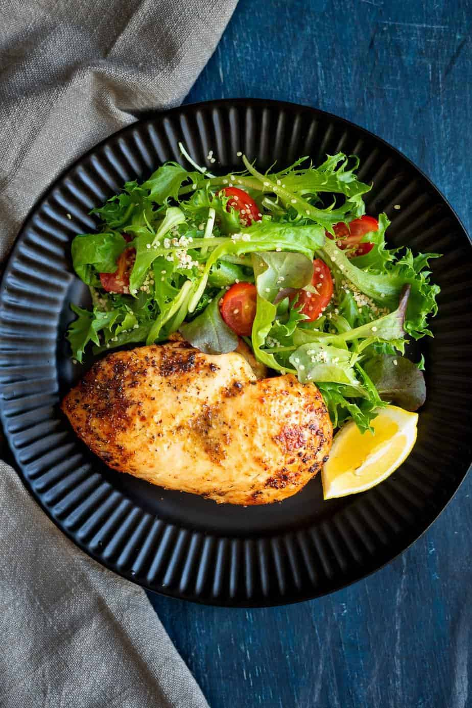 Excellently cooked chicken served with a salad of baby lettuces blend and cherry tomatoes.