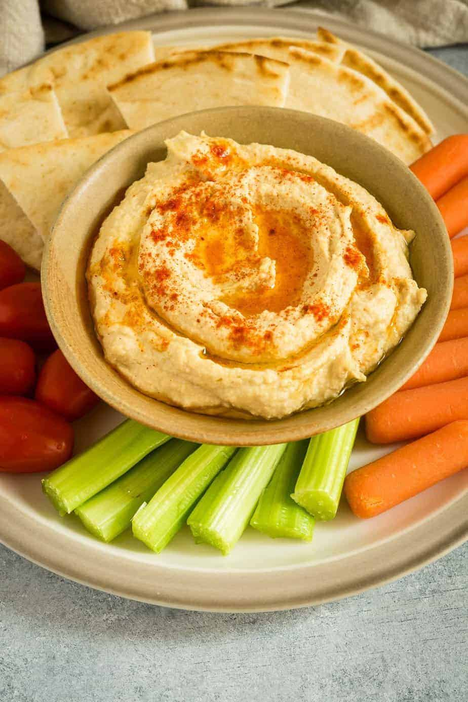 instant pot hummus serve with pitta bread, carrots, celery and cherry tomatoes.