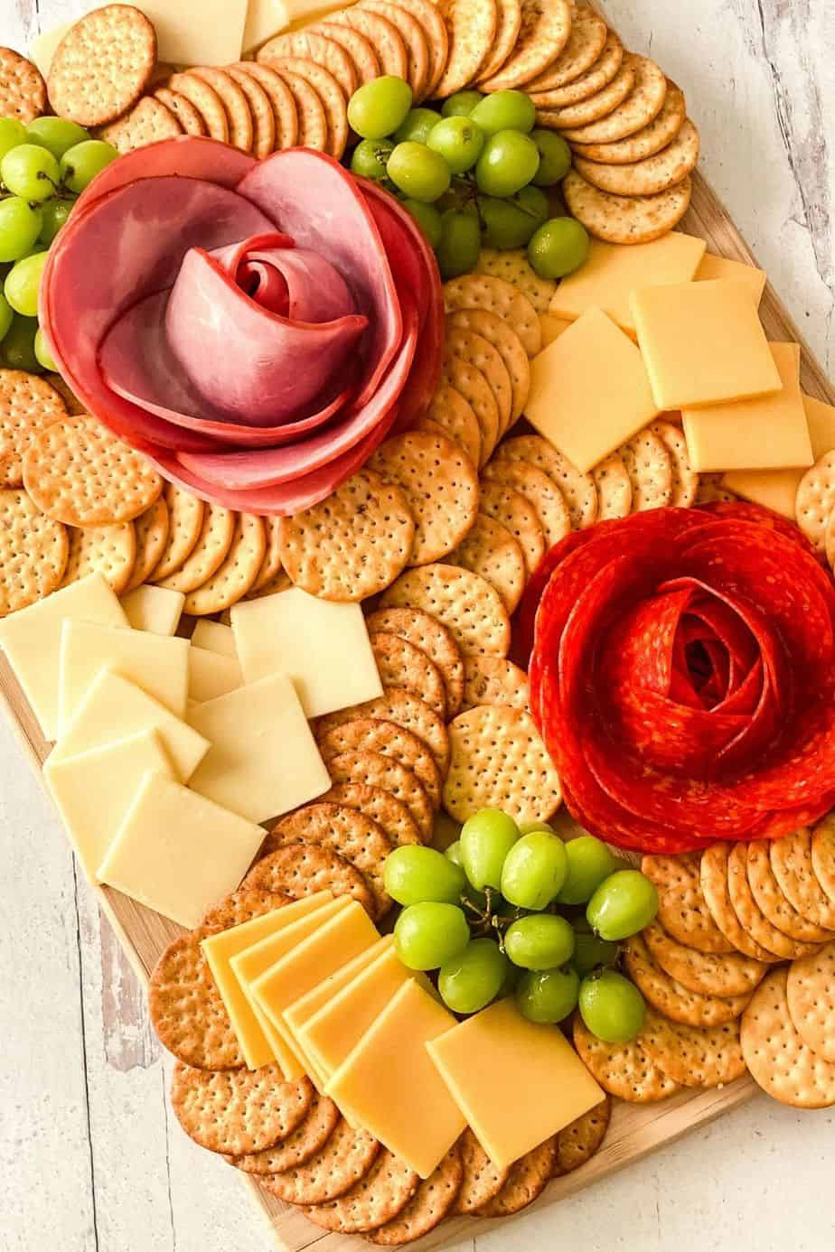 Dazzle your guests with this easy charcuterie board idea. Learn how to make a Charcuterie Board With Meat Flowers. It looks fancy but these meat flowers are easy to make. This is an easy party idea!