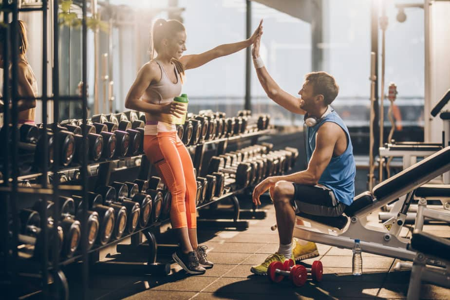 A girl and boy are supporting each other at the gym