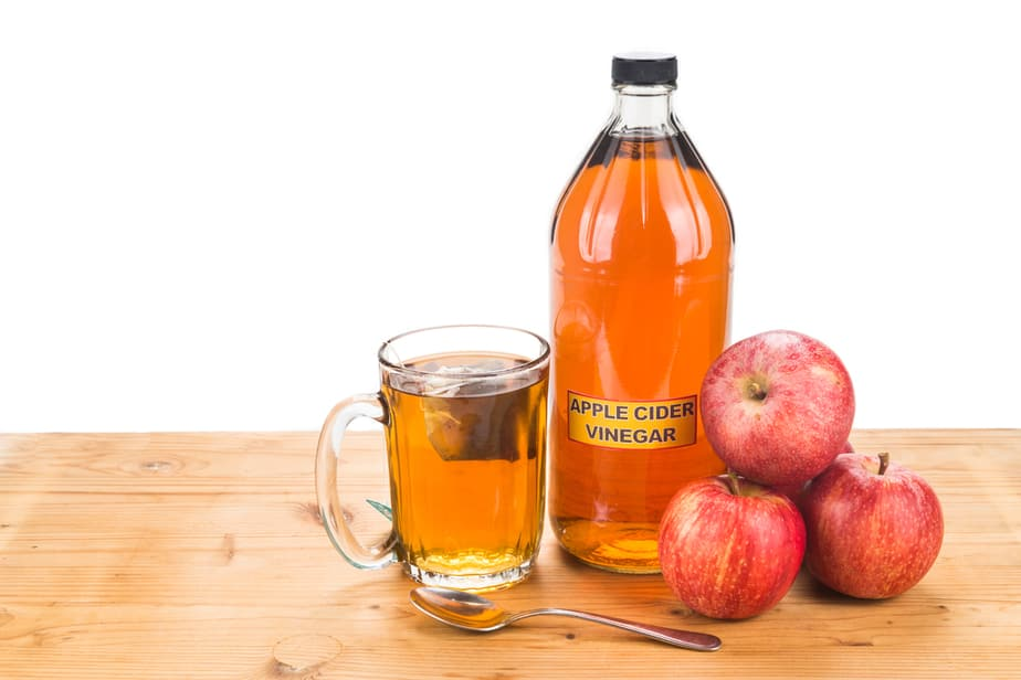 A spoon, a bottle, and a glass of apple cider vinegar with tree apples