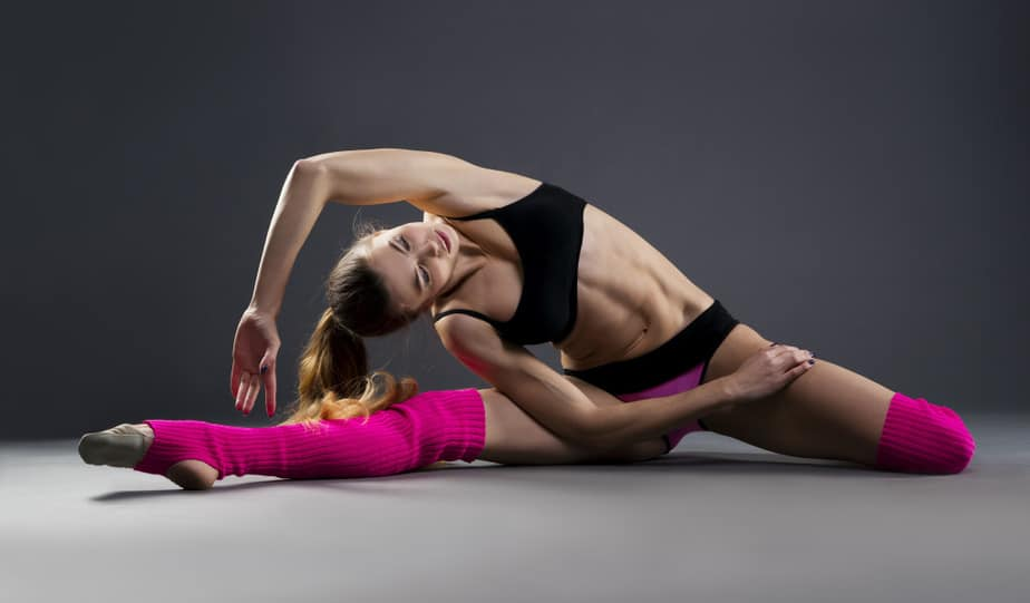 A girl has a stretching exercise before a training