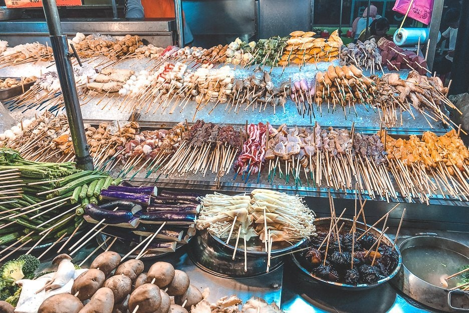 Satay sticks with meat and vegetables are lined up at a food stall, Kuala Lumpur