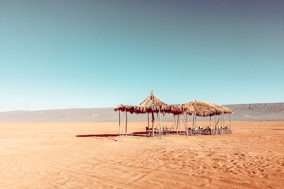 Chairs and palm tree shade covers in the Sahara Desert, Morocco