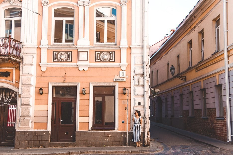 Jasmine stands in front of a pale pink building in the streets of Vilnius