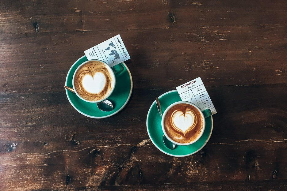 Two regular whites with coffee origin cards at Bocca Coffee