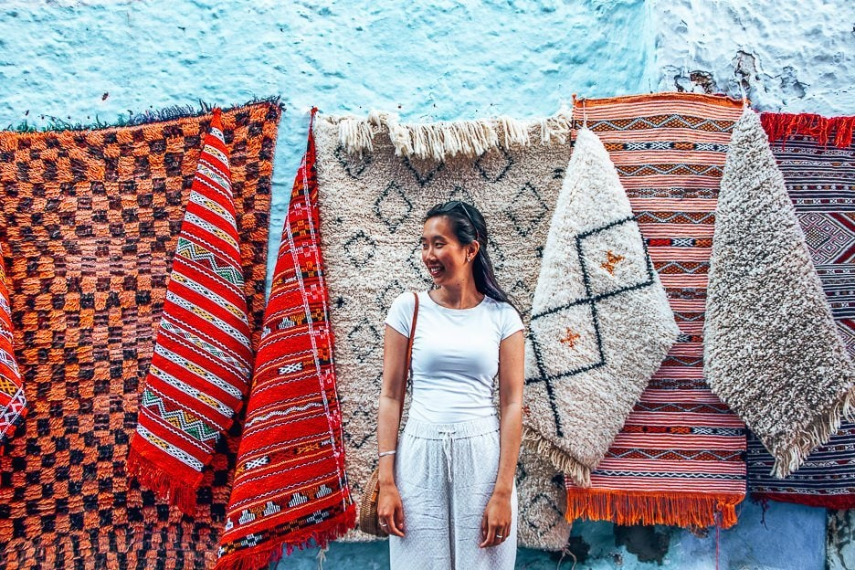 A woman wearing white stands in front of colourful woven rugs in Chefchaouen, Morocco