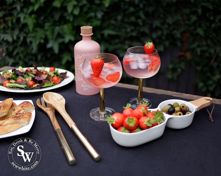 5 pieces from Elys Wimbledon Homeware to create a sophisticated summer table. Gold stemmed gin and tonic glasses, handled server, gold salad servers and navy tablecloth.