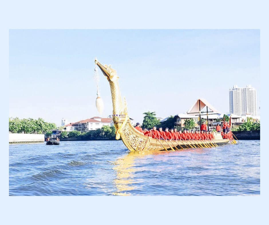 Golden swan is the bow of the gilded boat and points toward camera. ^0+ Thai Navy men dressed in traditional red regalia sit in the longboat. Blue water in foreground