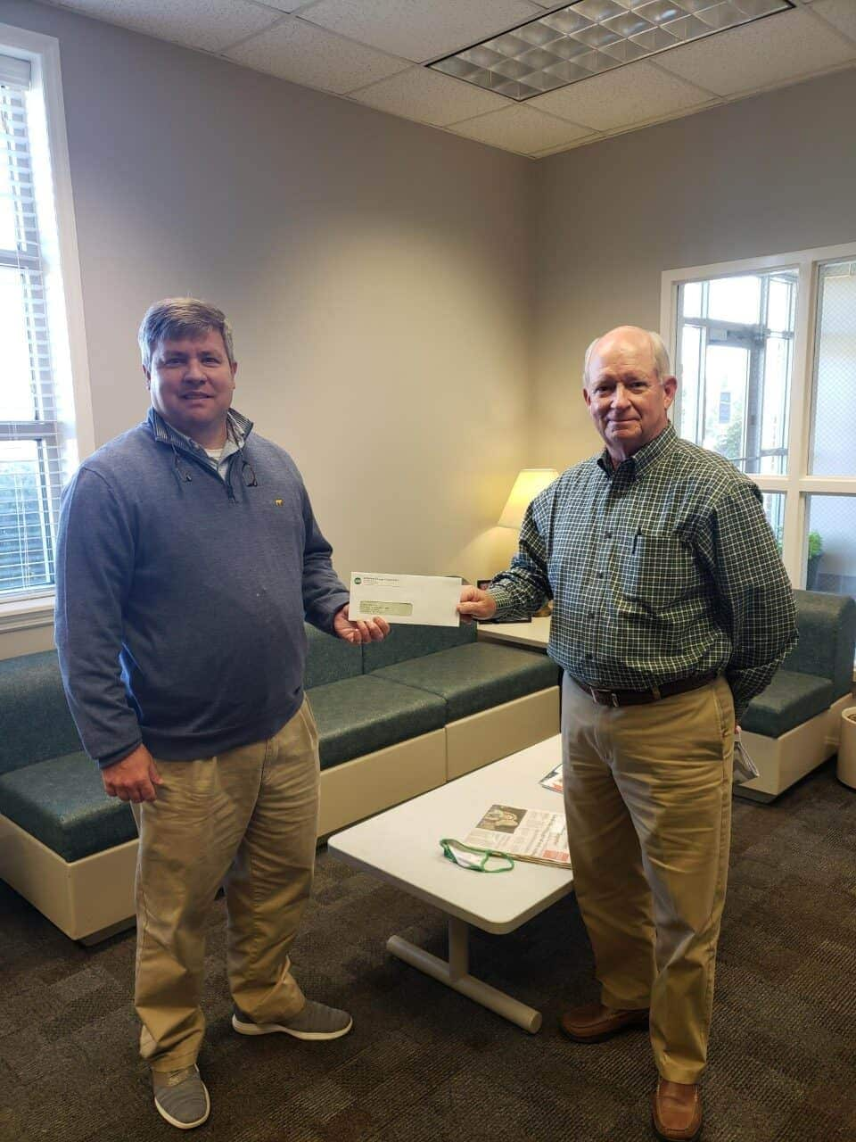 OFTC's Jefferson County Center Director, Matt Hodges (L), receives the donation from Jefferson EMC Vice President, William Irwin.
