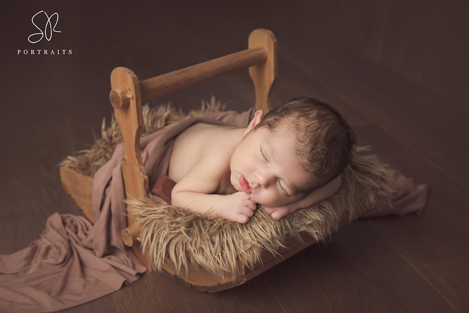 Newborn photography baby in wooden prop