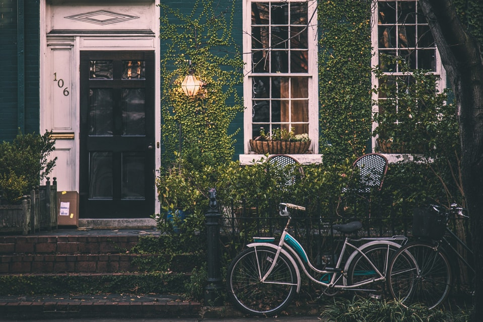 A vintage bicycle in front of a home
