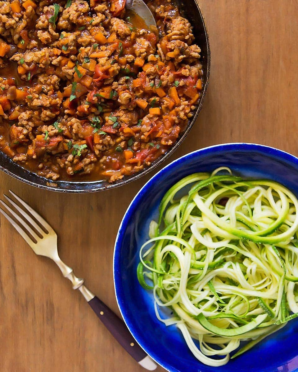 Pan of bolognese sauce next to zoodles bowl