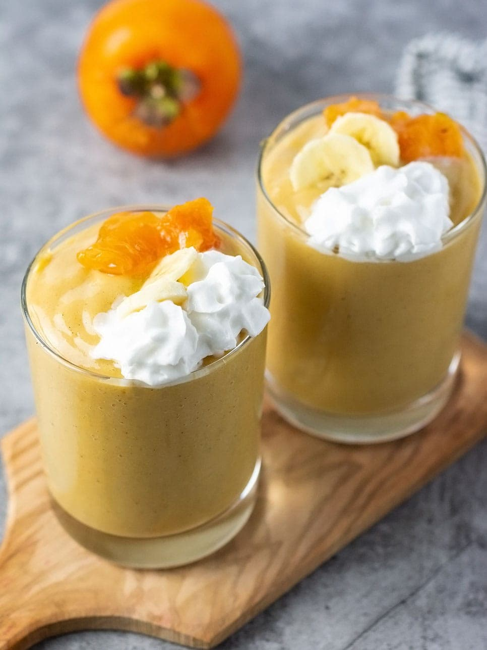 Persimmon smoothie in 2 glasses on wooden cutting board garnished with whipped cream and persimmon