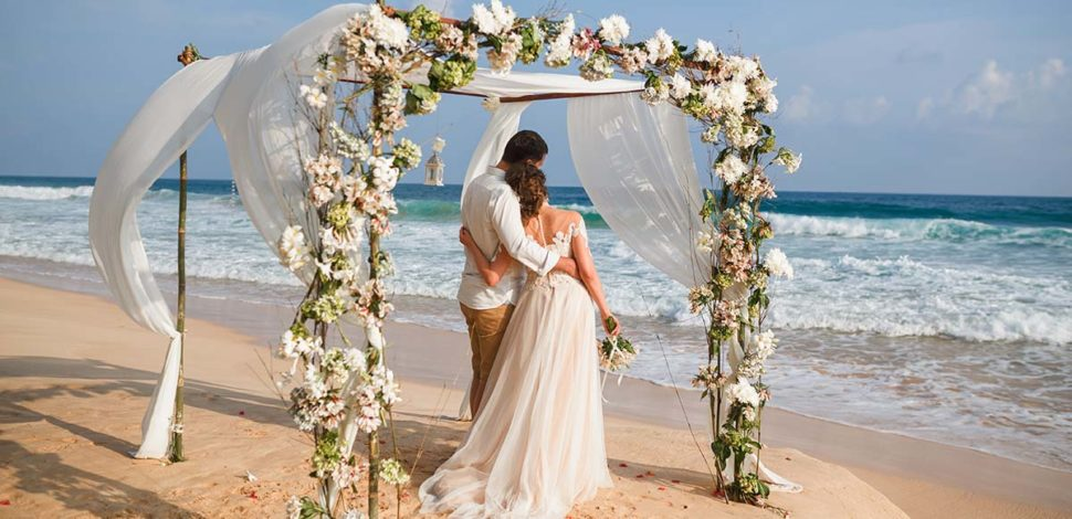 Beach wedding arch decorated with green and white flowers. By Marco Island Florist.