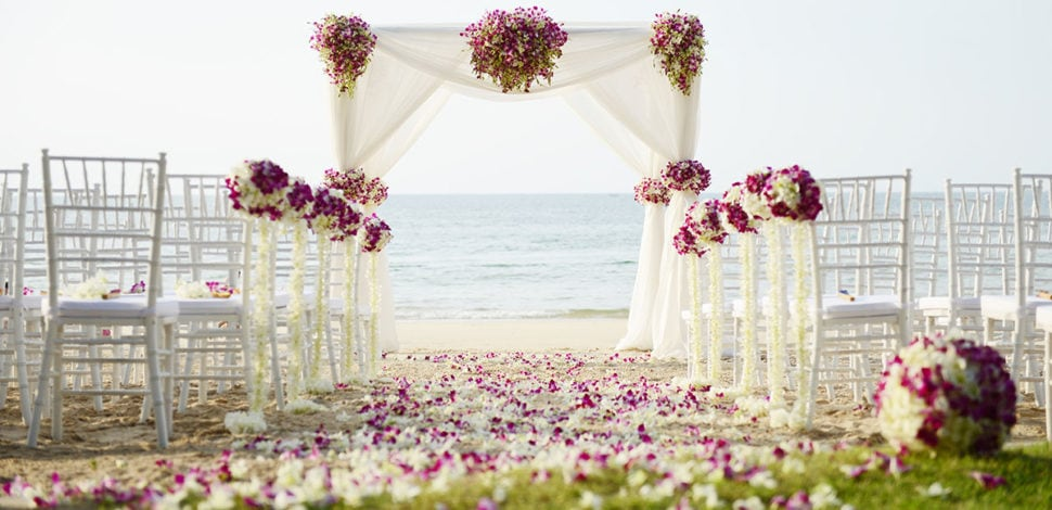 Beach wedding set up with chairs and an arch. Chairs are decorated with purple and white flower balls; arch is decorated with purple and white flowers and drapery. Purple and white petals line the aisle. Flowers by Marco Island Florist.