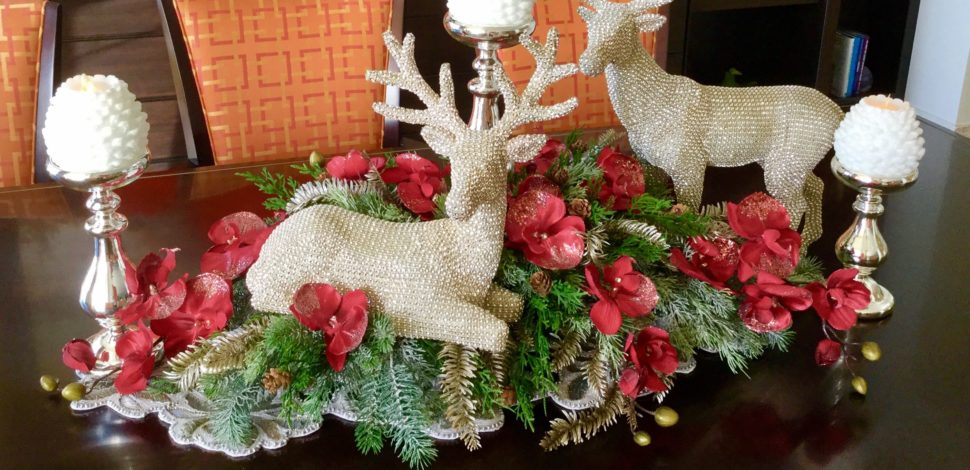 Holiday centerpiece of pine boughs, red orchids and glittering reindeer decorations. By Marco Island Florist.