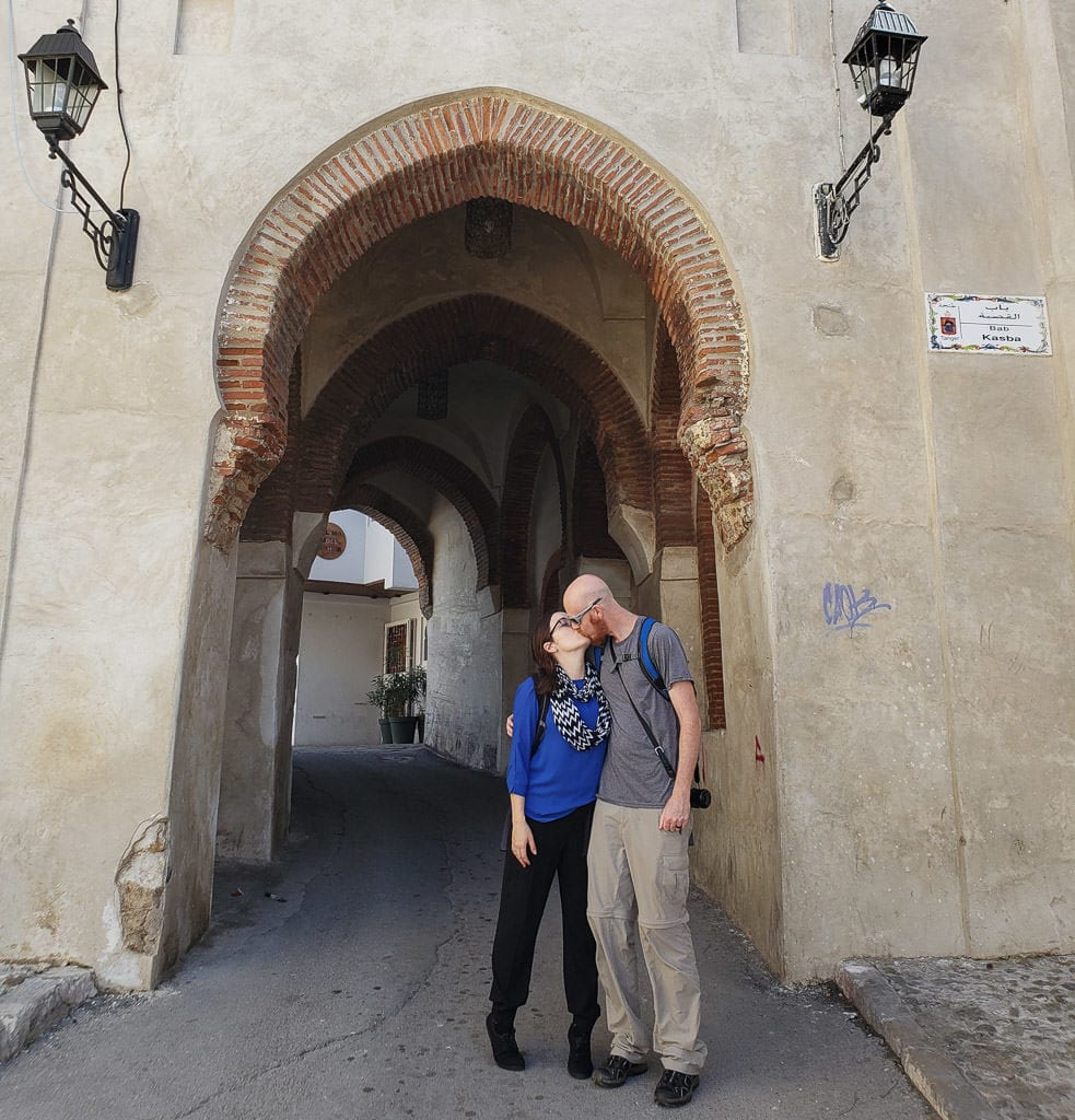 kissing in front of medina arch in tangier on day trip to Morocco tour
