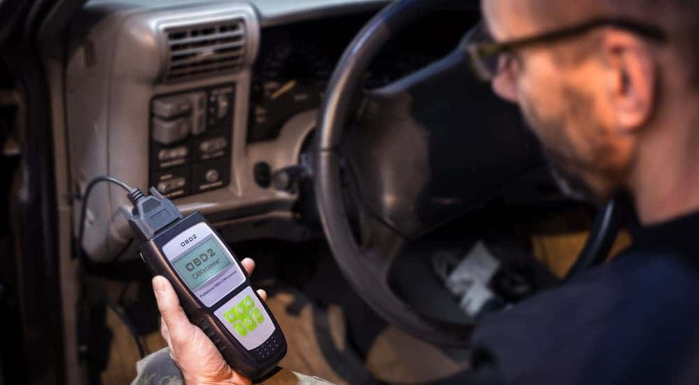 A mechanic is testing the OBD system with a code reader, the first thing you do when starting a car electrical repair.