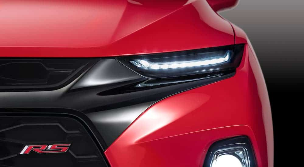 A close up of the front headlight of a Chevy SUV is shown.
