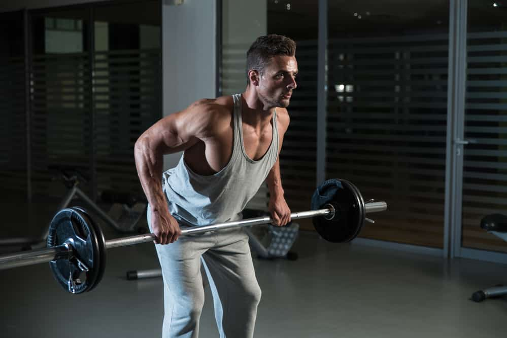 hombre haceindo remo con barra en el gimnasio