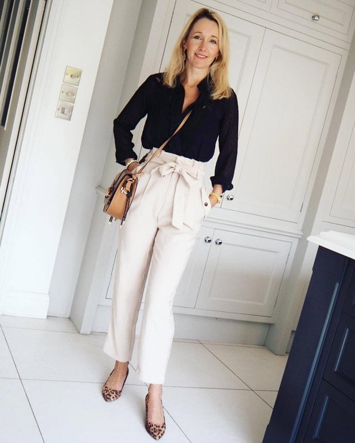 Karen wearing a black blouse and tie waist white pants | 40plusstyle.com