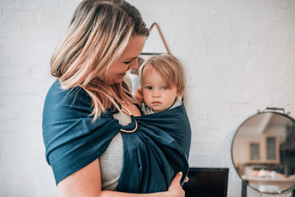 Mother wearing her child in a ring sling carrier