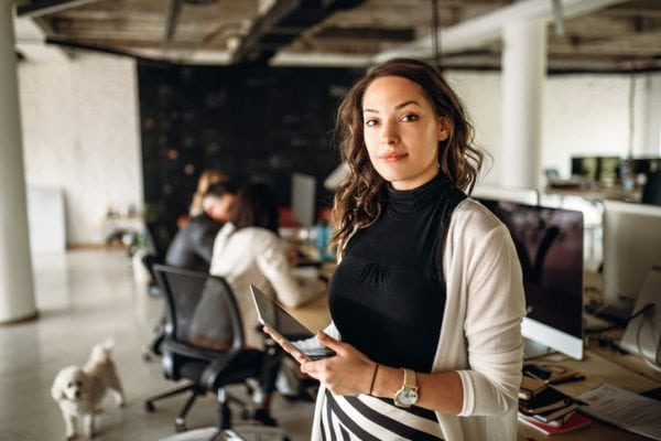 Portrait of a young business woman in the modern office, and a team behind her