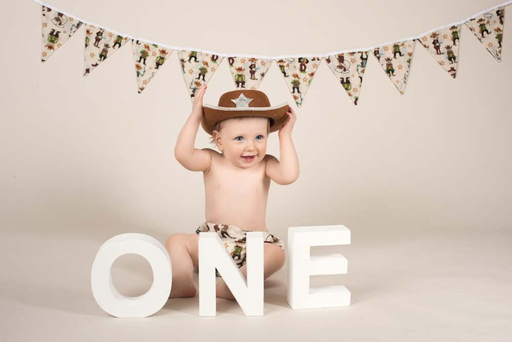 Baby boy in cowboy hat in front of cowboy bunting sitting behind large white letters O, N and E