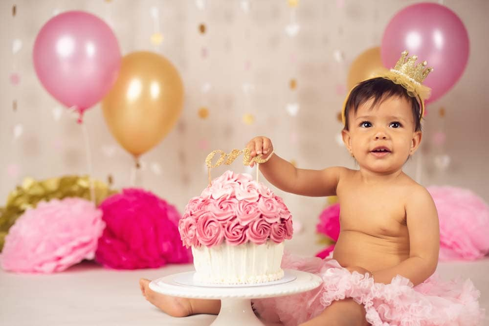 One year old sitting next to her pink birthday cake for her cake smash