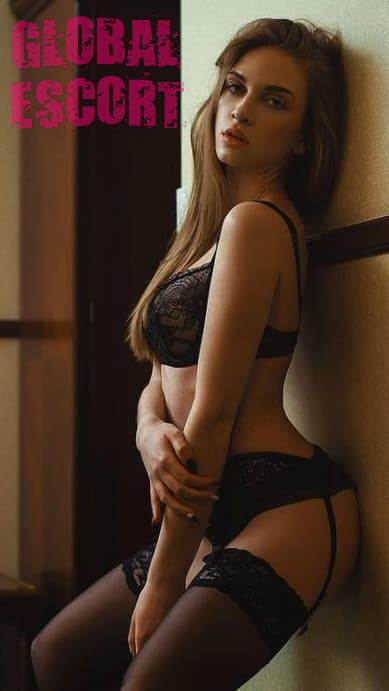 Sexy brown-haired woman in a photo session in transparent black lingerie in a room.