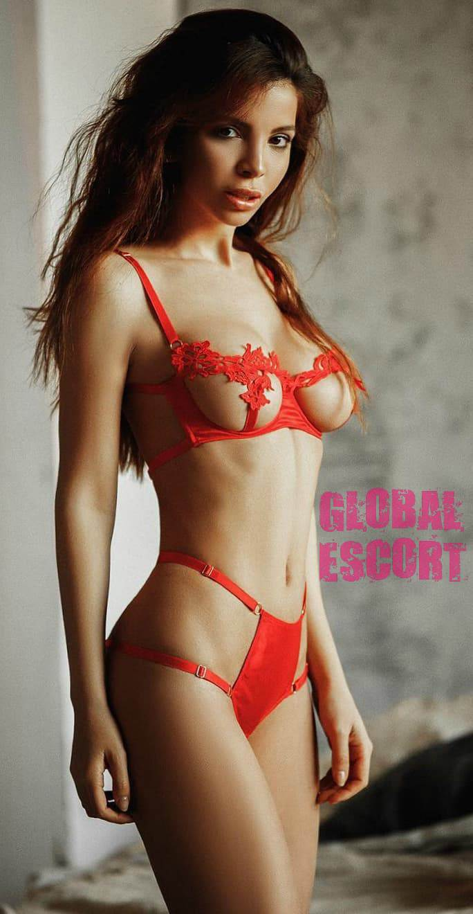 sexy escort model in transparent red lingerie in a gray room