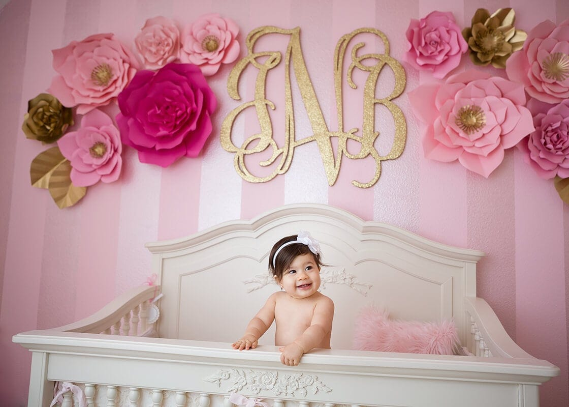 baby in her crib with flowered wall and monogram