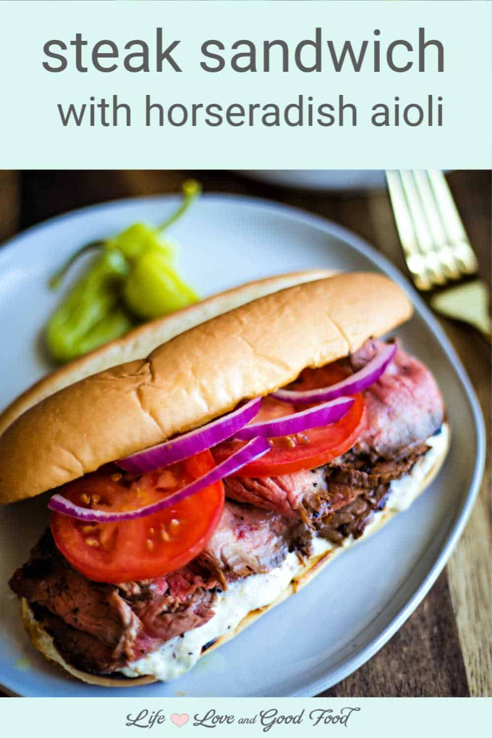 This mouth-watering steak sandwich recipe is piled high with tender grilled flank steak and dressed with horseradish aioli, sliced tomatoes, and red onions.