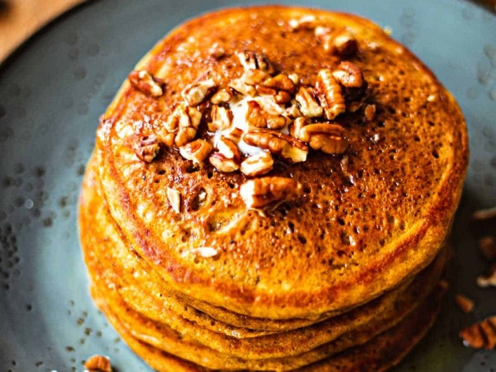 Pumpkin Spice Pancakes with maple syrup and toasted pecans on a blue plate