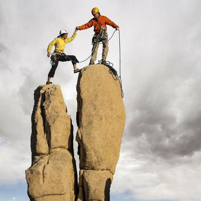 Man helping Woman climb a rock