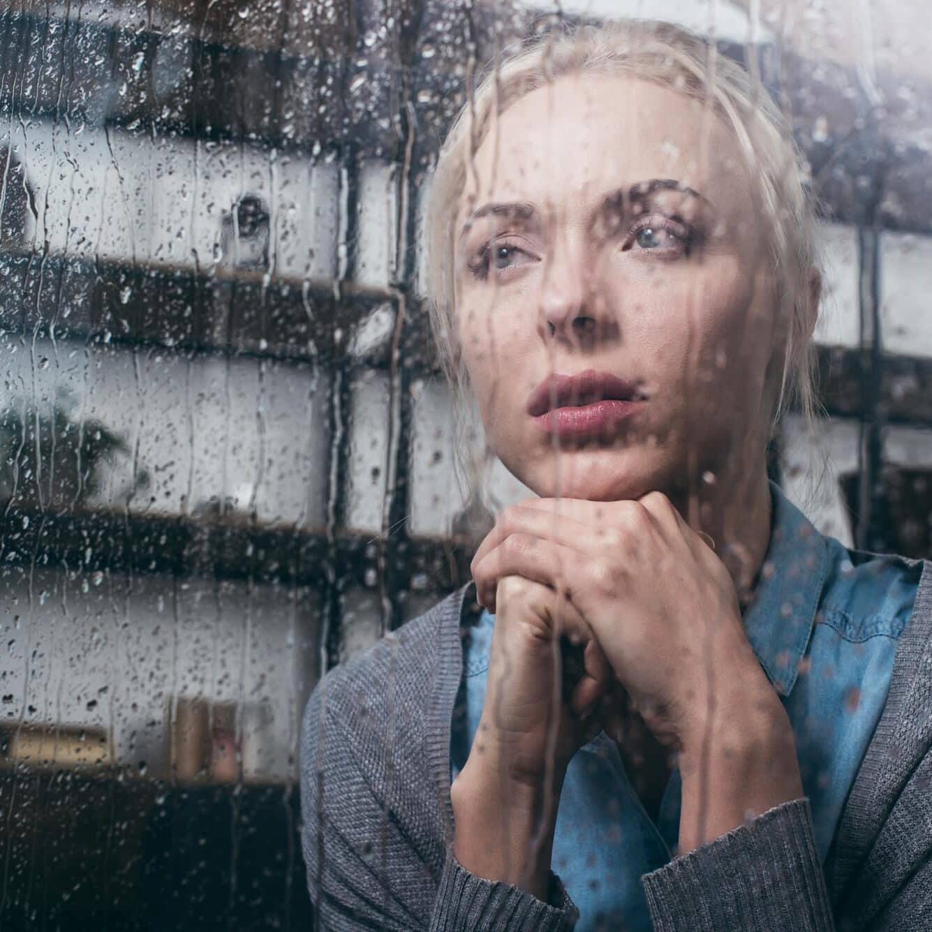 Women looking out rainy window