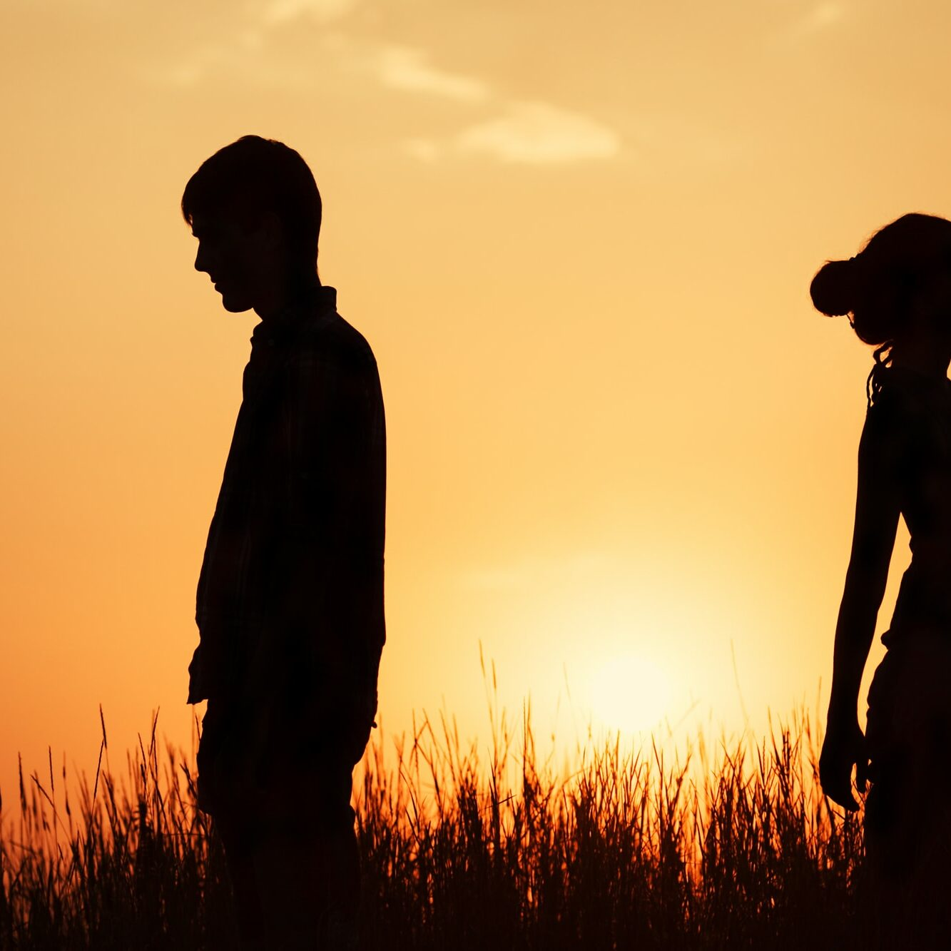 couple standing against the sunset back to back