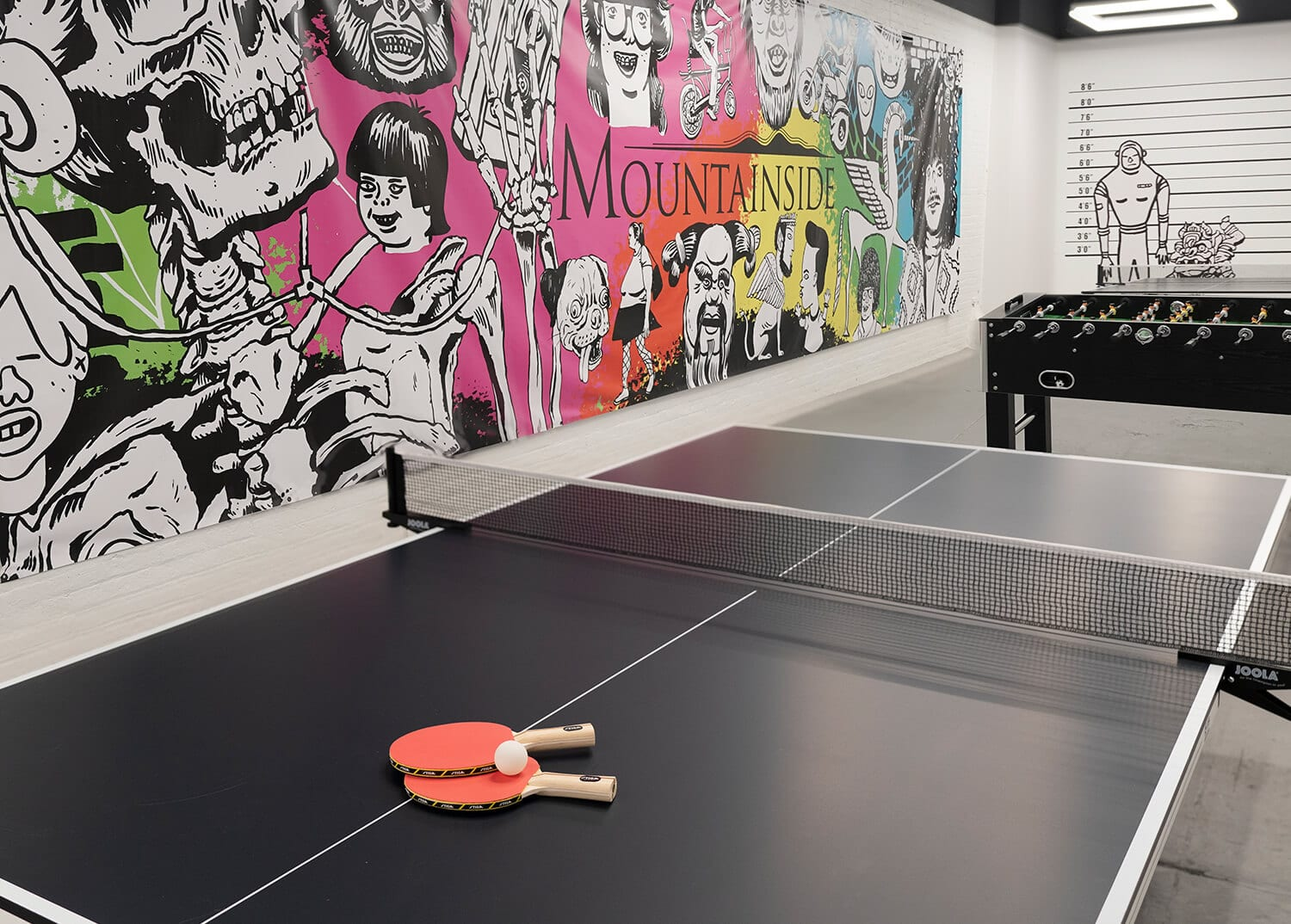 A game room with ping pong and other games with bright wall mural in NYC.