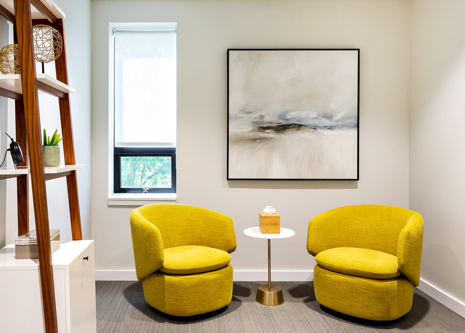 A comfortable therapy room with bright yellow arm chairs and small table. Mountainside Addiction Treatment Center- Huntington, NY.