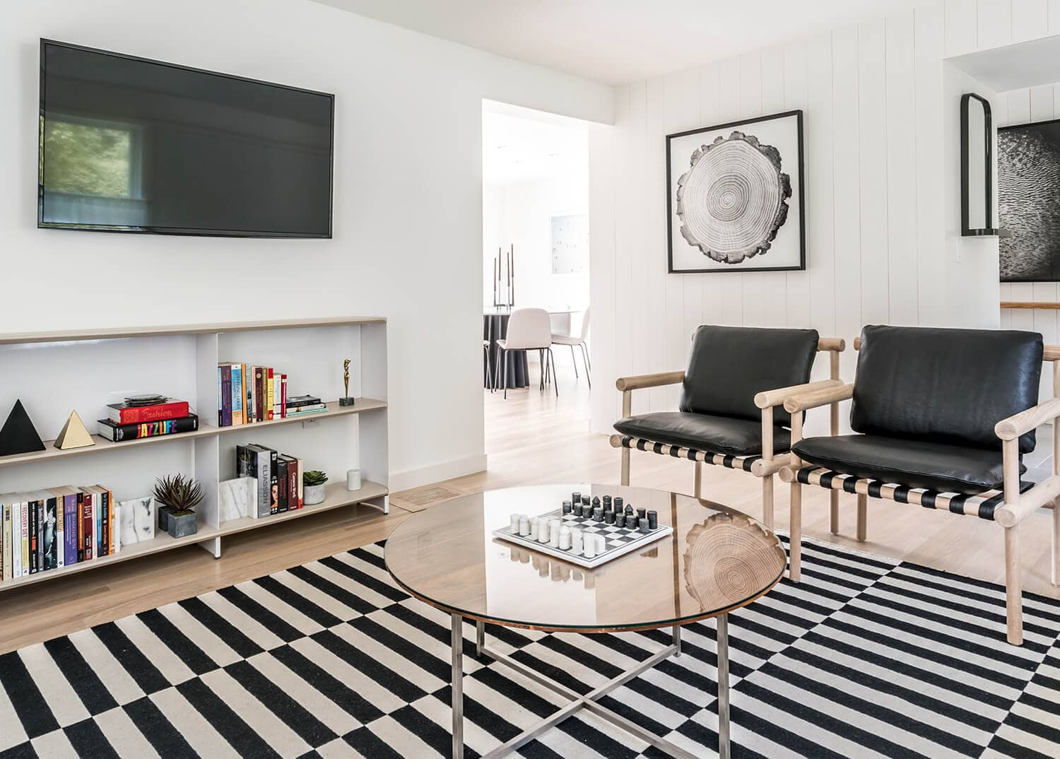 A contemporary living area with modern furniture and black-and-white decor, including a bold area rug. Mountainside Sober House.