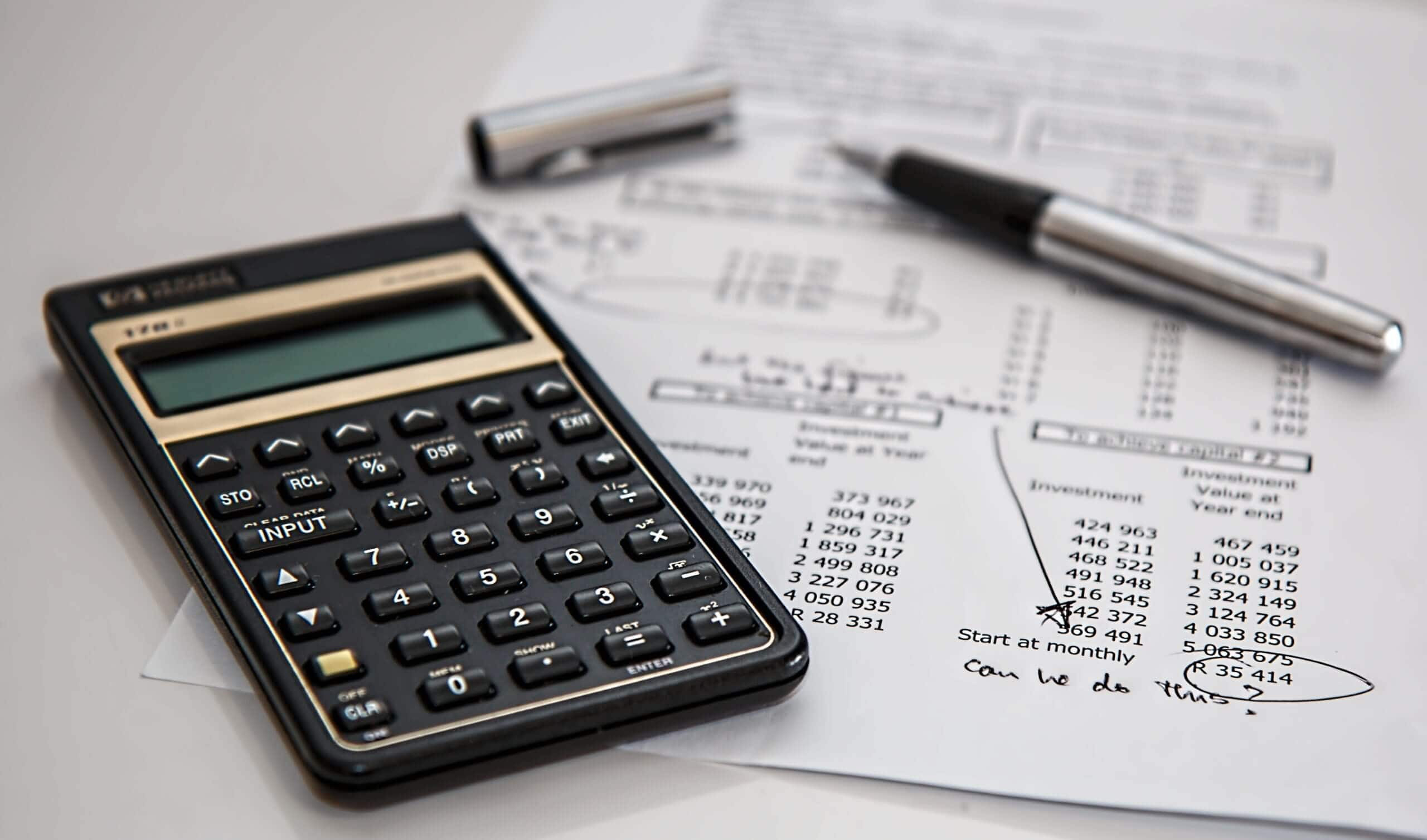 Desk with calculator with budget planning paper- Pexels stock image