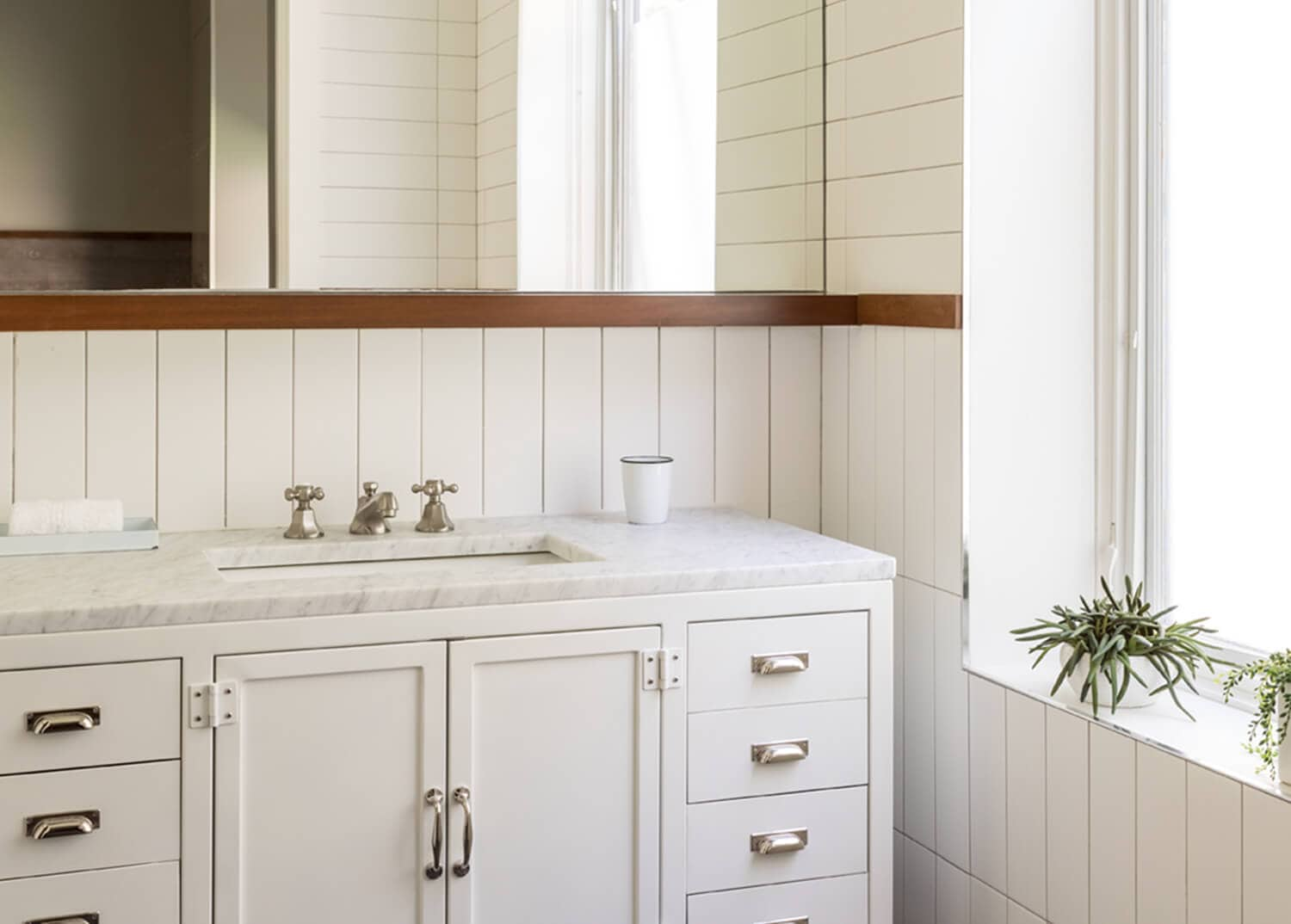 A country-style all-white bathroom with beautiful shiplap walls and white cabinetry at Mountainside Treatment Center