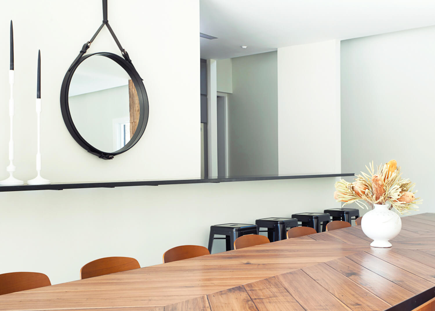 A clean and contemporary common dining area with a large dining table and round mirror hanging on the wall.