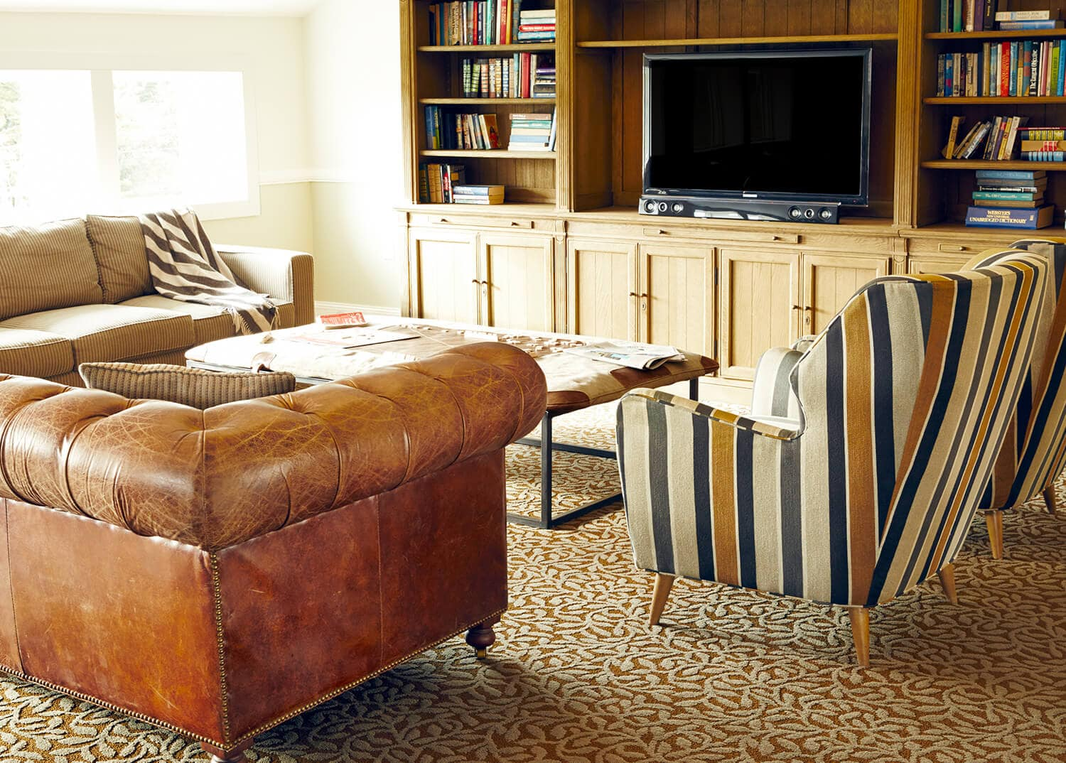 Men's lounge with leather furniture and warm decor at Mountainside Treatment Center in Canaan, CT.